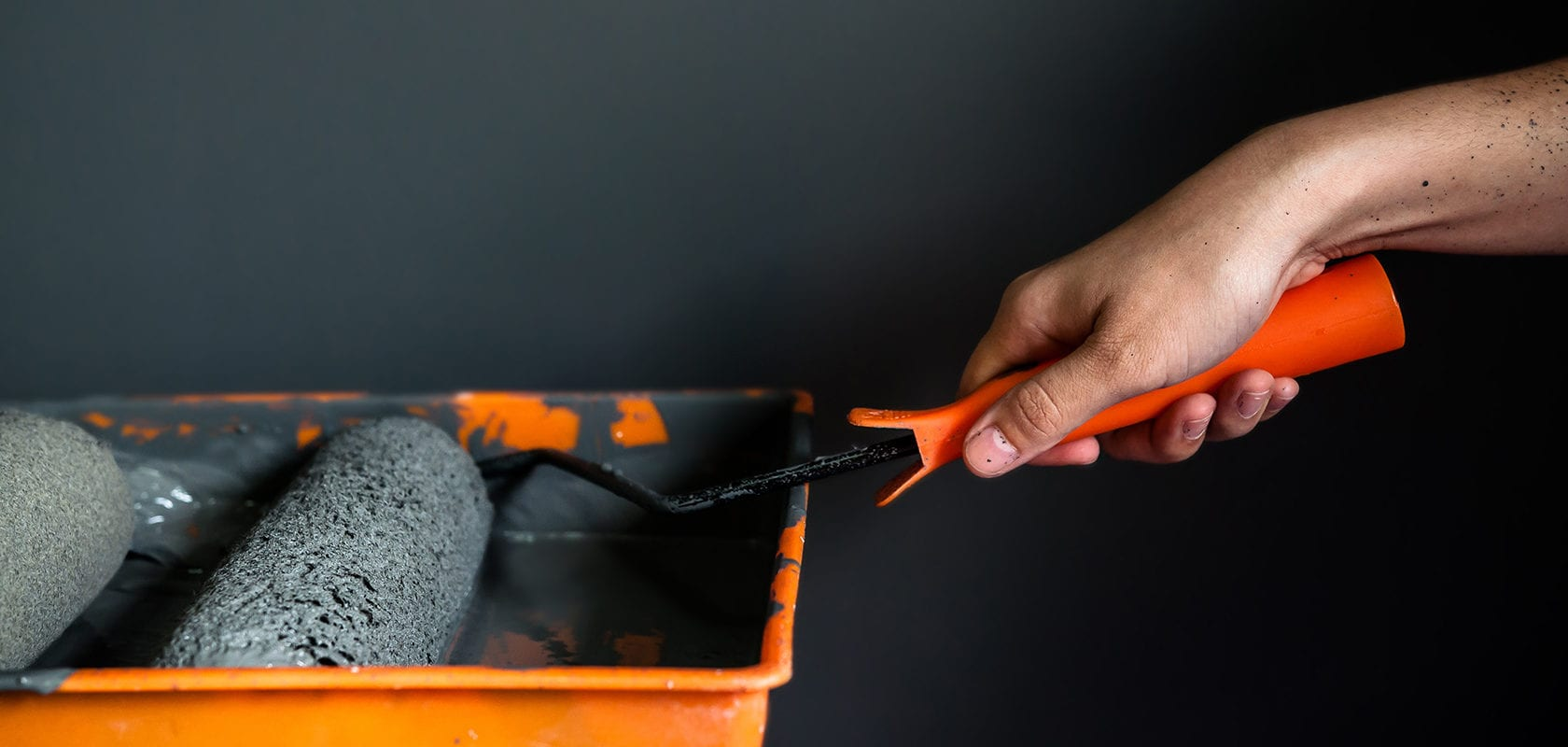 Close up of hand holding paint roller in paint tray, Grey wall background
