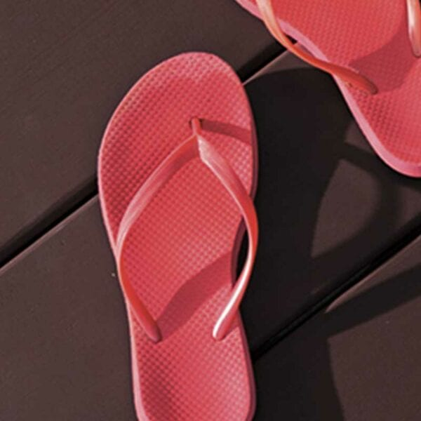 red flips flops on brown stained deck