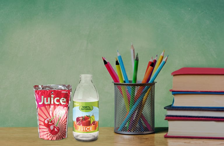 A desk with a chalkboard in the background, there is a stack of books, pencils in a holder and 2 juice containers on it.