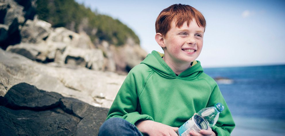 A young red headed boy in a green hoodie sitting on a rock along the ocean.